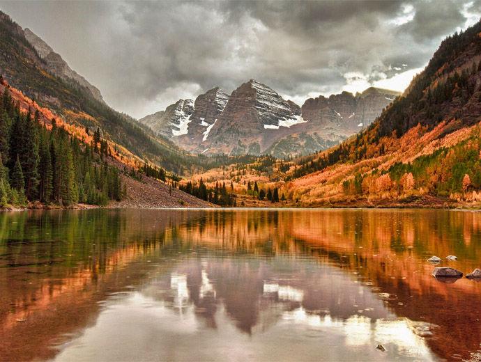 Есенни багри край бреговете на река, а насреща са високи планински върхове.