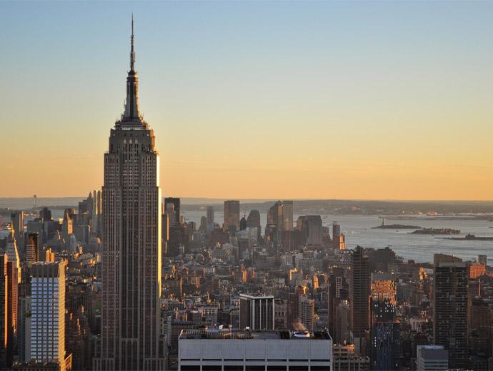 Емпайър Стейт Билдинг в Ню Йорк по залез слънце. Долу в далечината се вижда Статуята на свободата.