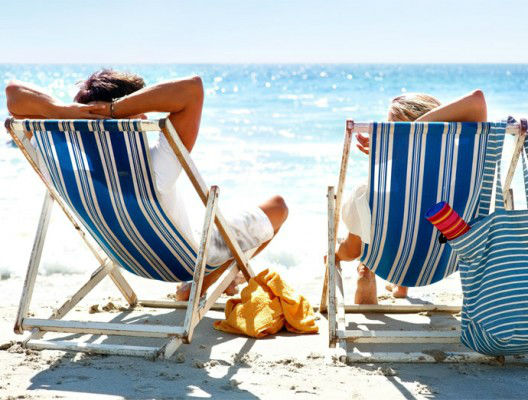 Идеалната почивка - двама души на шезлонг на плажа.