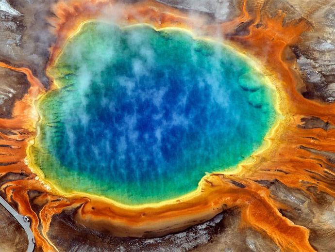 Големият призматичен извор в Йелоустоун гледан от горе, обагрен от пъстри цветове.