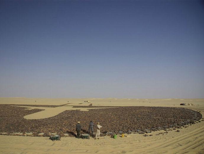 Снимка от земята на Мемориала за загиналите от UTA 722. Виждат се очертанията на самолет сред тъмните камъни.