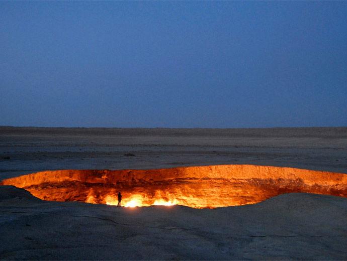 Вратата към ада край Дарваз, Туркменистан. Виждат се пламъците от дупката по залез.
