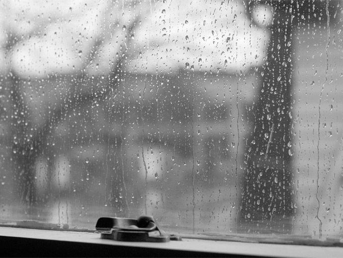 Дъждовни капки се стичат по затворения прозорец.