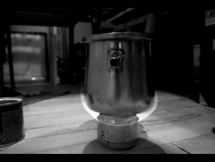Готовият котлон за планина с метален съд за вода отгоре. Черно-бяла снимка.