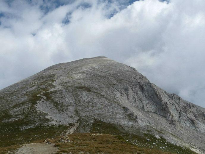 Сиви облаци са обгърнали стръмната пирамида на връх Вихрен в Пирин.
