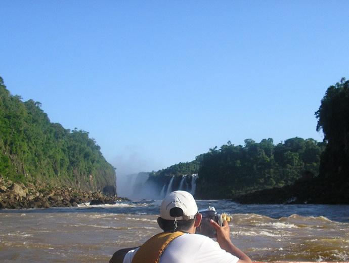 Макуко сафари сред водите на река Игуасу. Нагоре по течението се вижда и главната част от водопада.