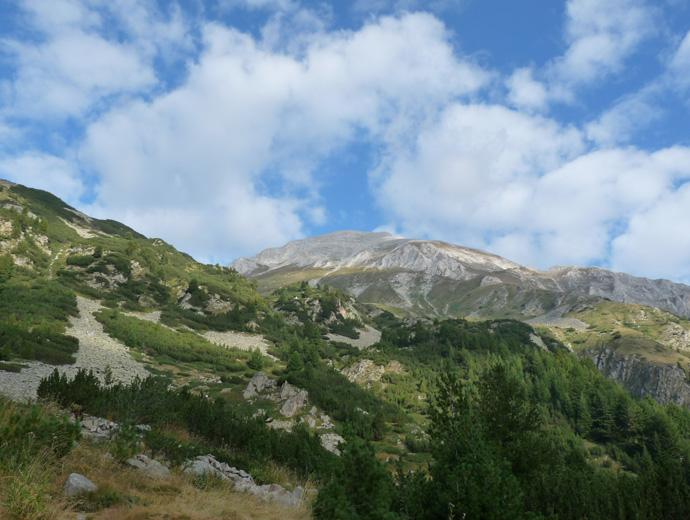 Връх Вихрен сниман от хижа Вихрен. Облаци частично закриват върха.